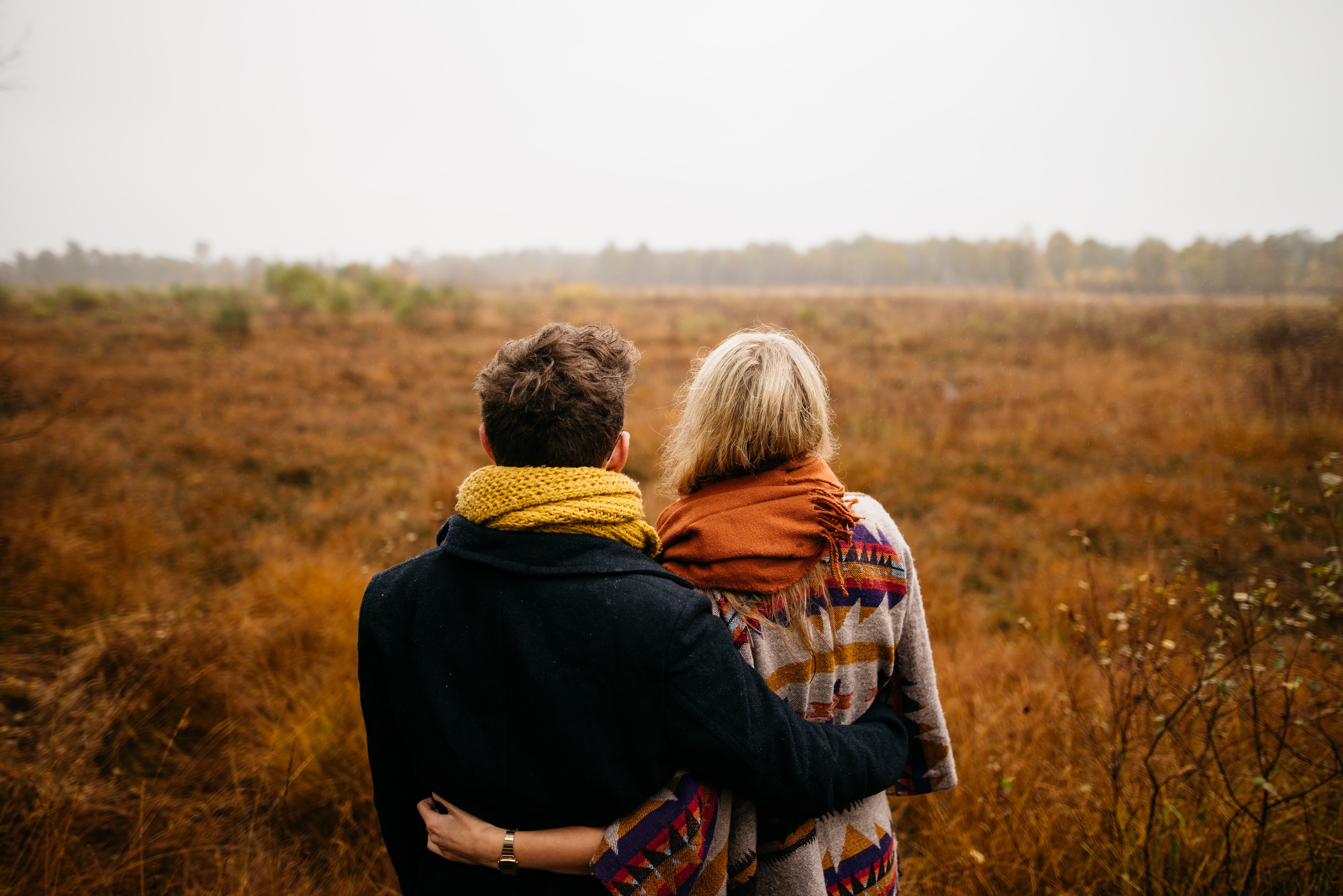 An image of a man and a woman holding each other whilst looking out to the distance, to represent the loved ones around you and how Blossom Ceremonies discusses their funeral ceremony wishes.
